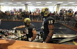 Josh Jelesky (69) and Archibald Barnes (15) come down the escalator at  Barnes and Noble with black uniforms and gold helmets. 2b84e36e7